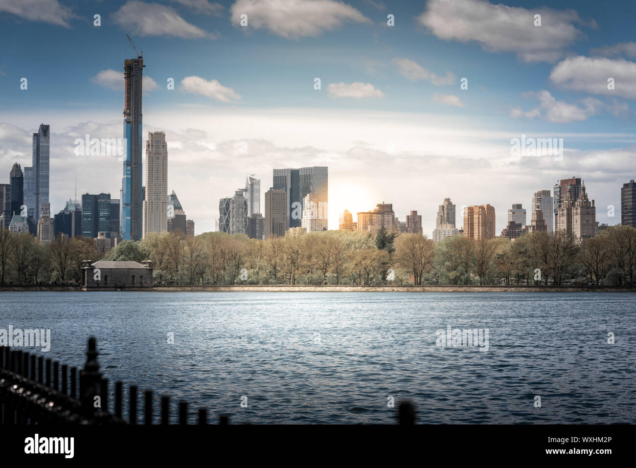 A shot of Central Park during a beautiful sunny day, with buidlings reflecting into the water of a lake. New York City, United States Stock Photo