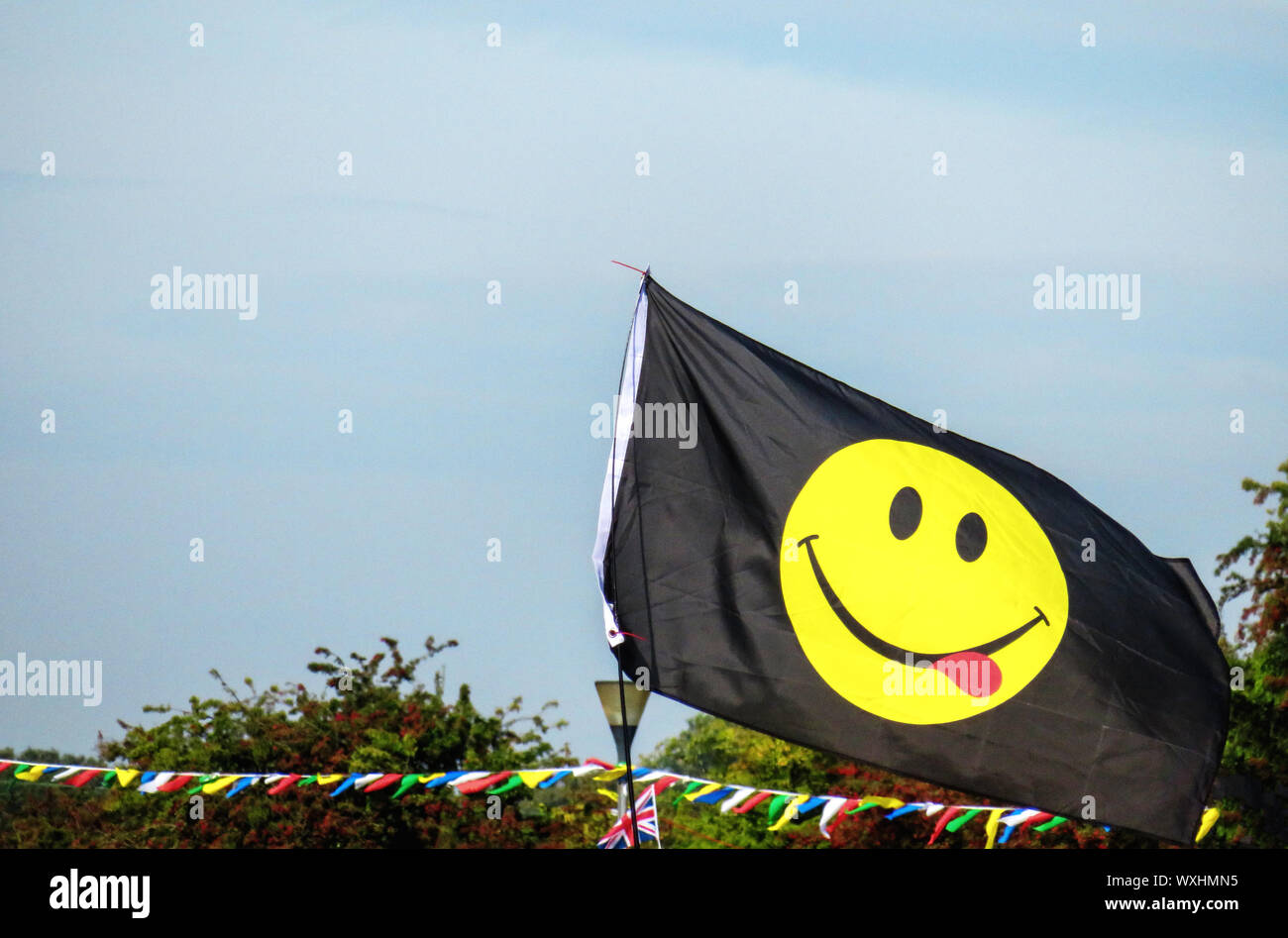 Yellow Smiling Face emoji on a black flag Stock Photo
