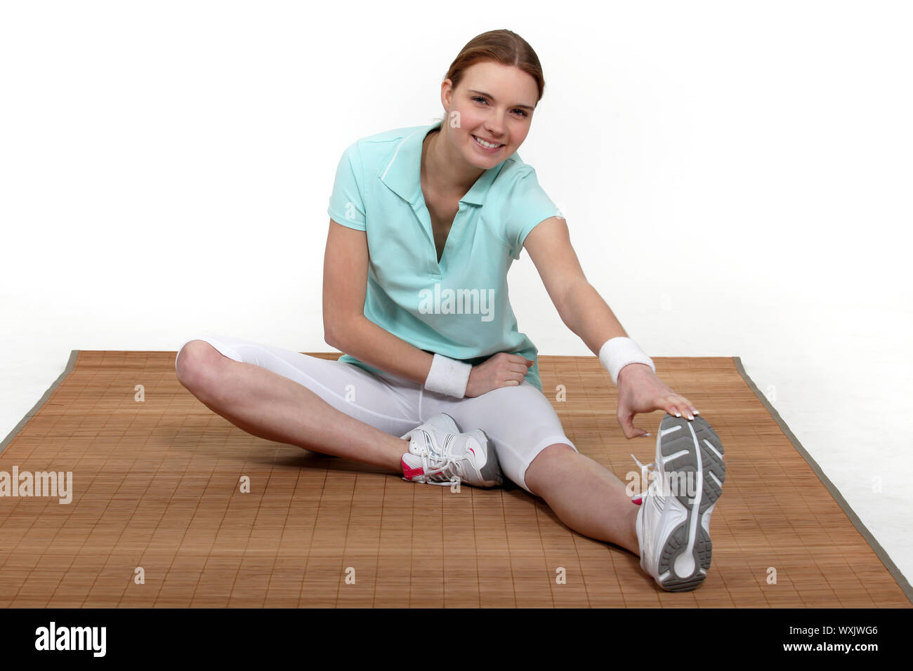Woman sitting stretching Stock Photo