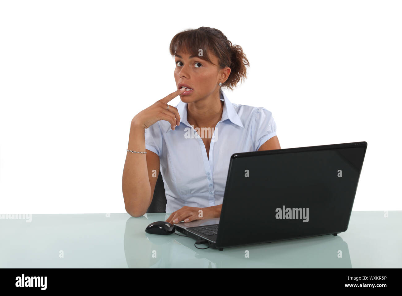 businesswoman sitting at her desk and thinking Stock Photo