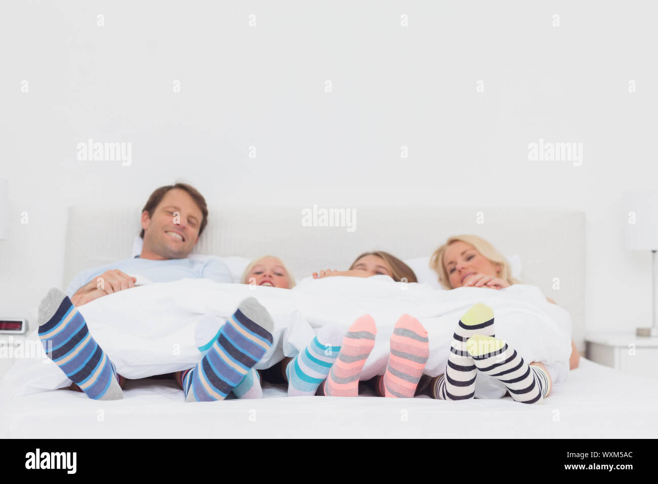 Family wearing stripey socks at home in bed Stock Photo