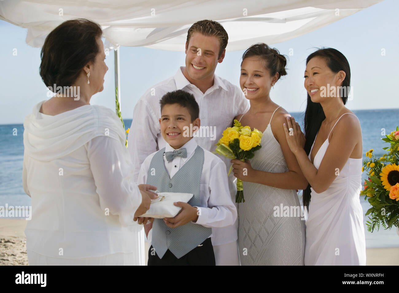 Bride and Groom on Beach With Family Stock Photo