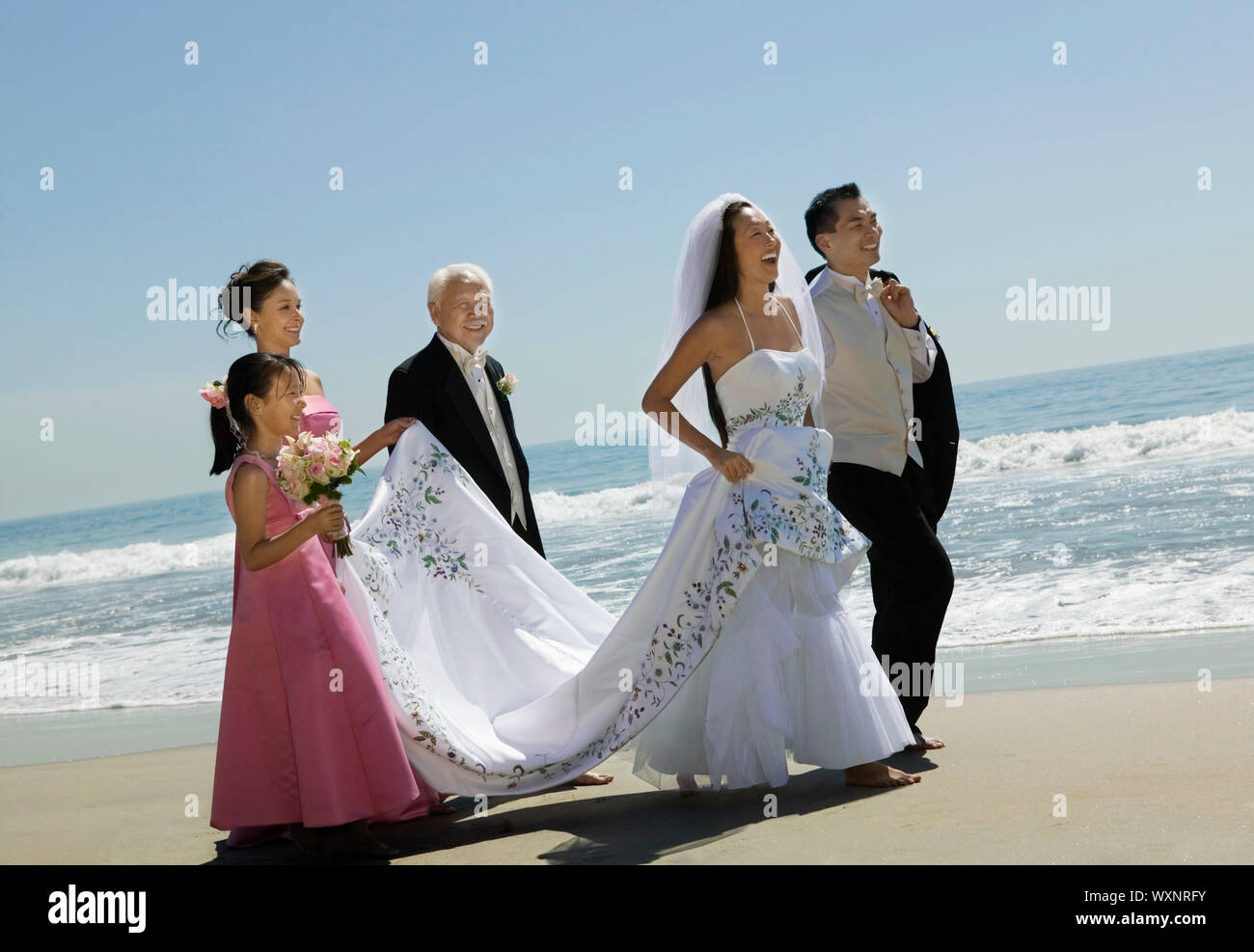 Bride and Groom With Family on Beach Stock Photo