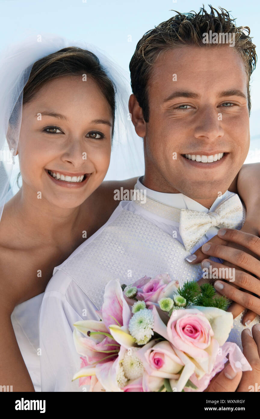 Bride and Groom With Bouquet on Beach Stock Photo