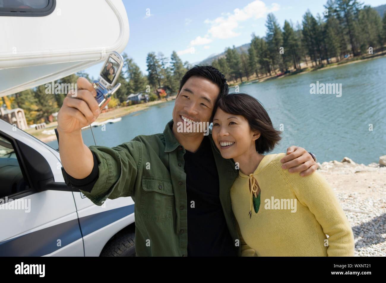 Couple Using Cell Phone Camera at Lake Stock Photo