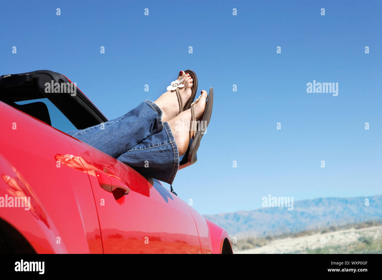 Feet Dangling Out of a Convertible Stock Photo