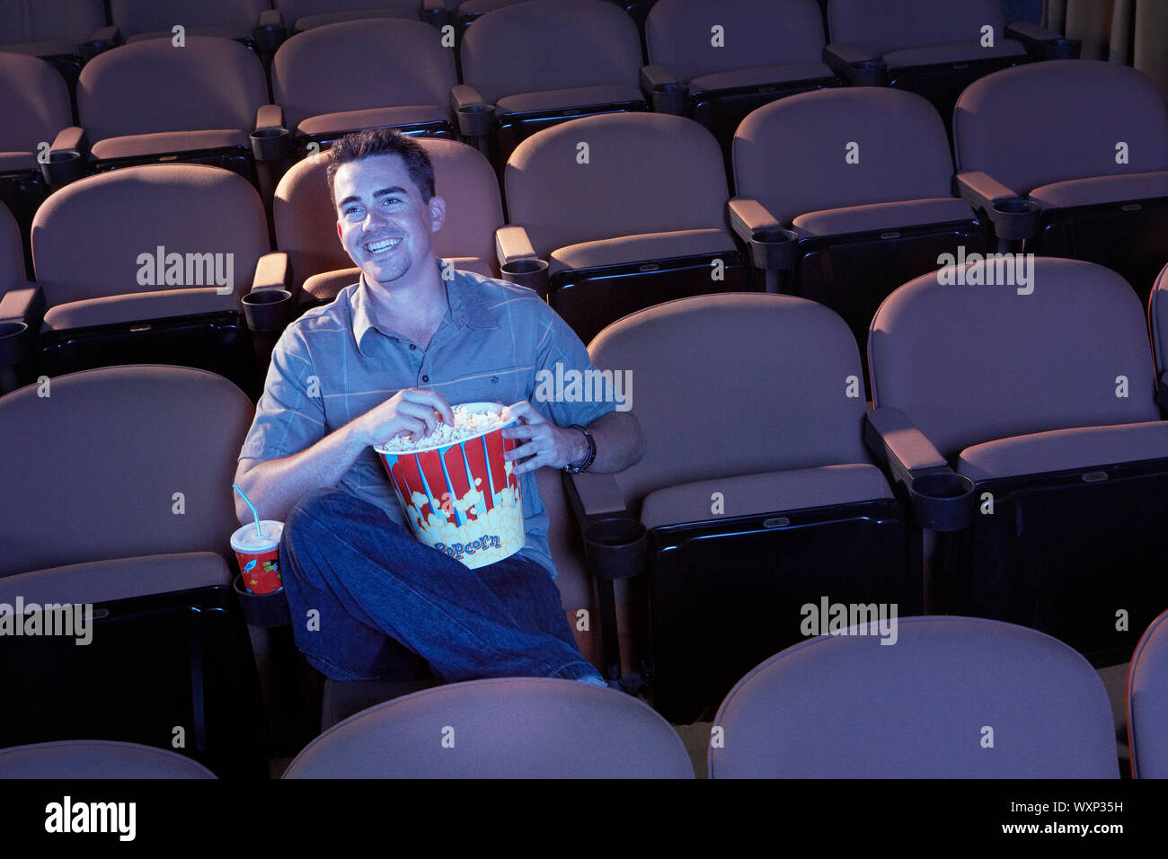 Man Watching Movie in Empty Theater Stock Photo