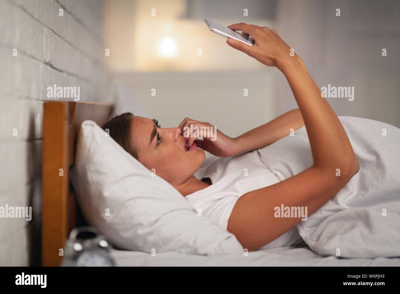 Scared Girl Holding Smartphone Lying In Bed At Home Stock Photo