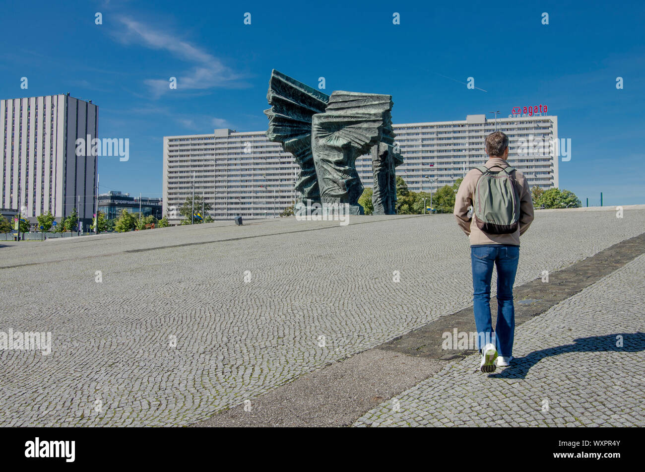 Katowice, Silesia, Poland; September 15, 2019:  A man sightseeing  the Monument of Silesian Insurgents with Superjednostka building in Katowice Stock Photo