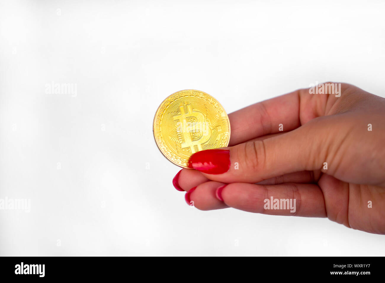 Virtual cryptocurrency money Bitcoin golden coin in the right hand of a woman with red nail polish. The future of money. Isolated on a white backgroun Stock Photo