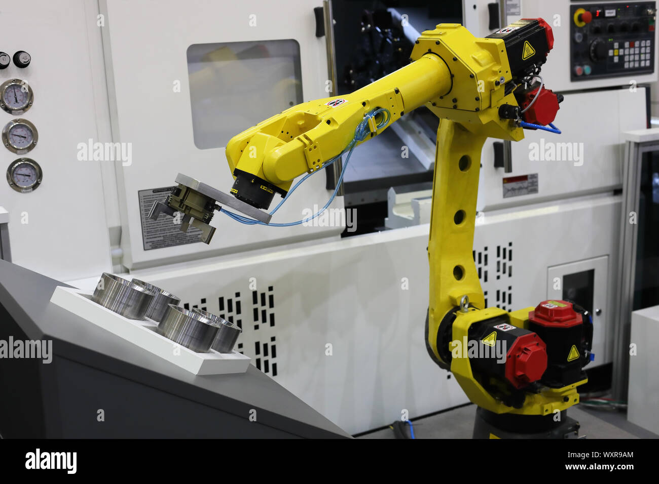 Automated CNC machine loading with robotic arm. Selective focus Stock Photo  - Alamy