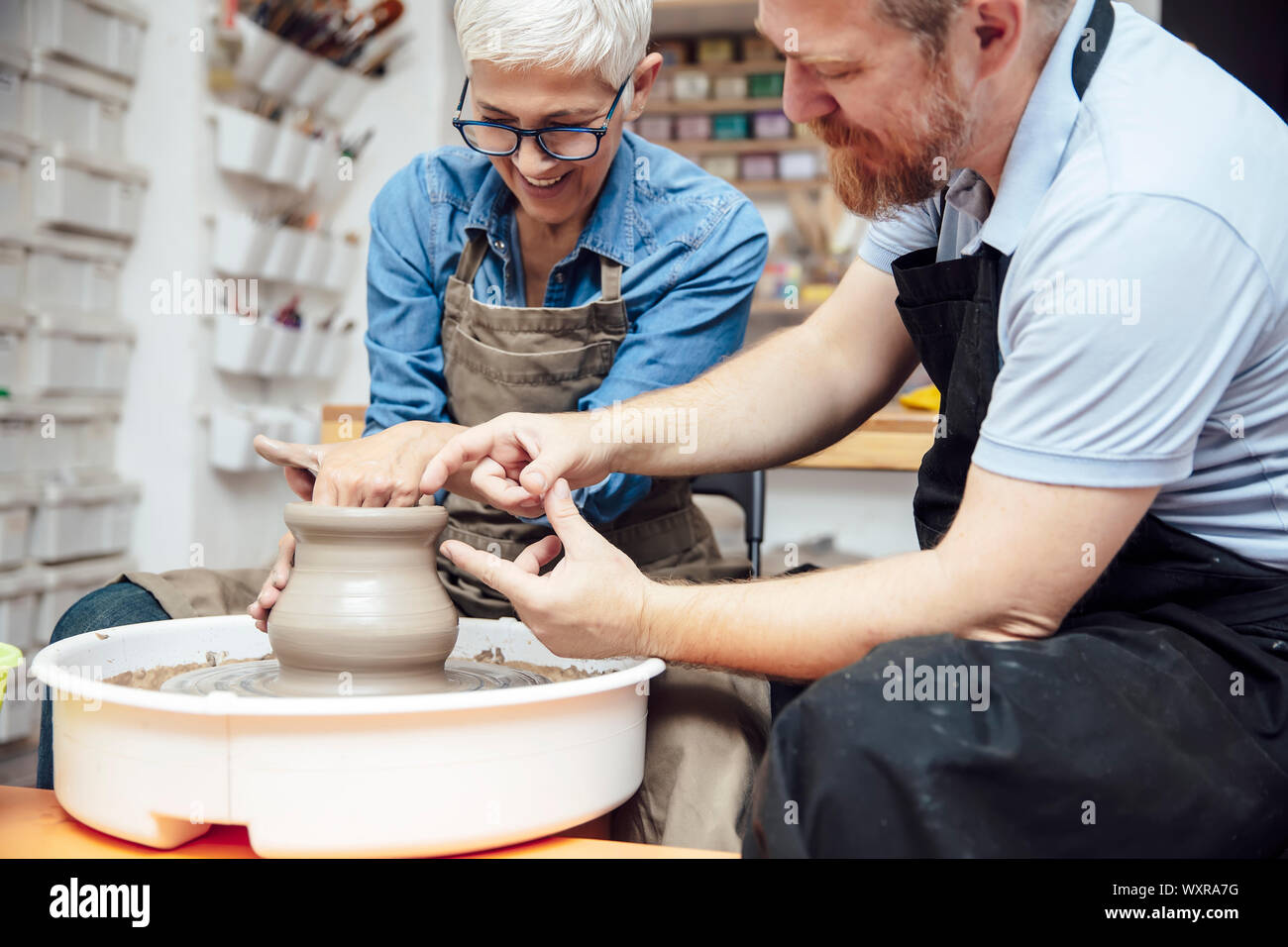 Senior woman spinning clay on a wheel with a help of a teacher at pottery class Stock Photo
