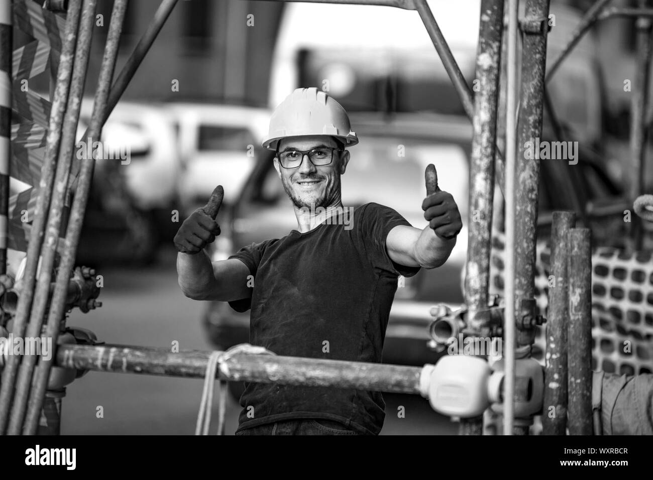 Young italian building worker, engineer smiling and showing thumb up. Streets of Sicily. Palermo / Italy Stock Photo