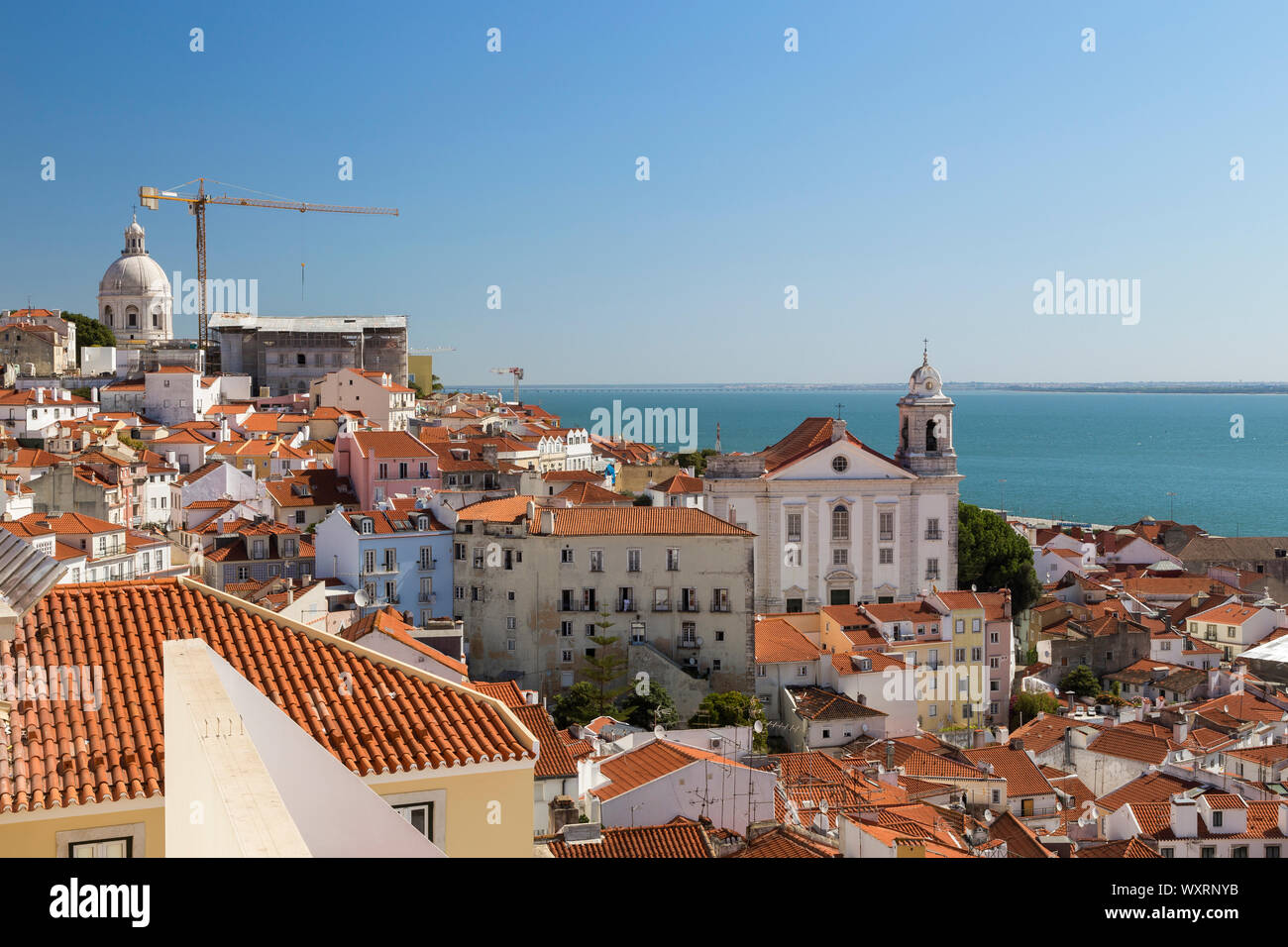 View of Tagus River and old buildings at the historical Alfama district in downtown Lisbon, Portugal. Viewed from Miradouro de Santa Luzia  viewpoint. Stock Photo