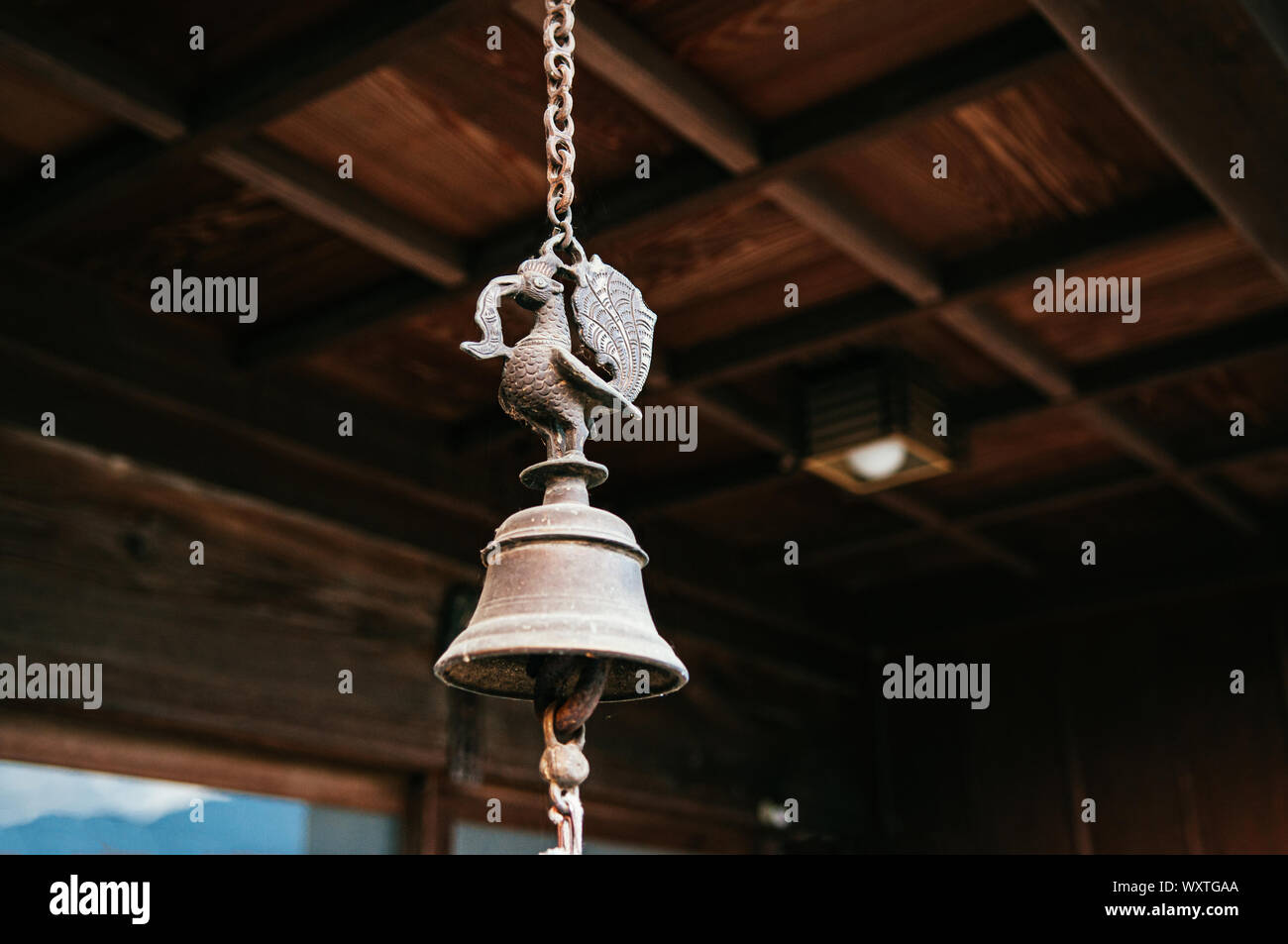 Japanese Buddhist temple or shinto shrine antique bronze bell hanging on metal chain under wooden ceiling. Stock Photo
