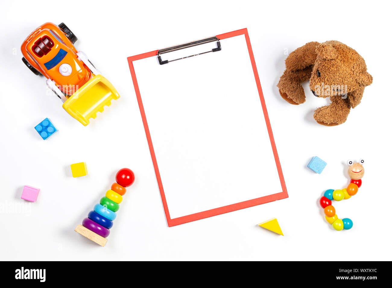 Colorful baby kid toys and red clipboard with blank sheet of paper on white background. Top view Stock Photo