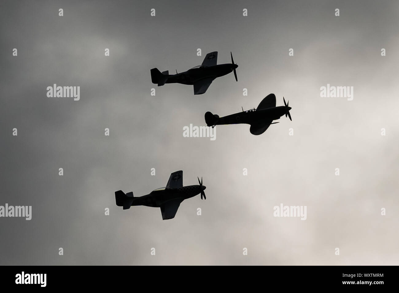 The vintage-themed Goodwood Revival. Britain's greatest annual classic car show. Rolls Royce Merlin Spitfire Mk IX (middle) and two P51D Mustang fighter planes take to the skies starting three days of action at what was once RAF Westhampnett. UK. Stock Photo