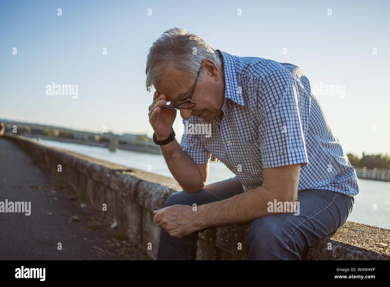 Outdoor portrait of senior man who is having headache. Stock Photo