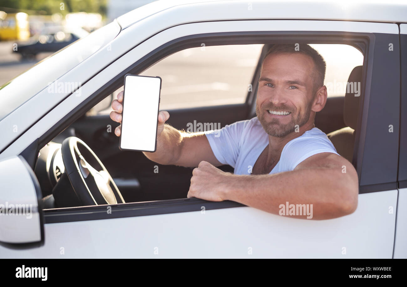 An attractive man in a car shows a smartphone. Stock Photo