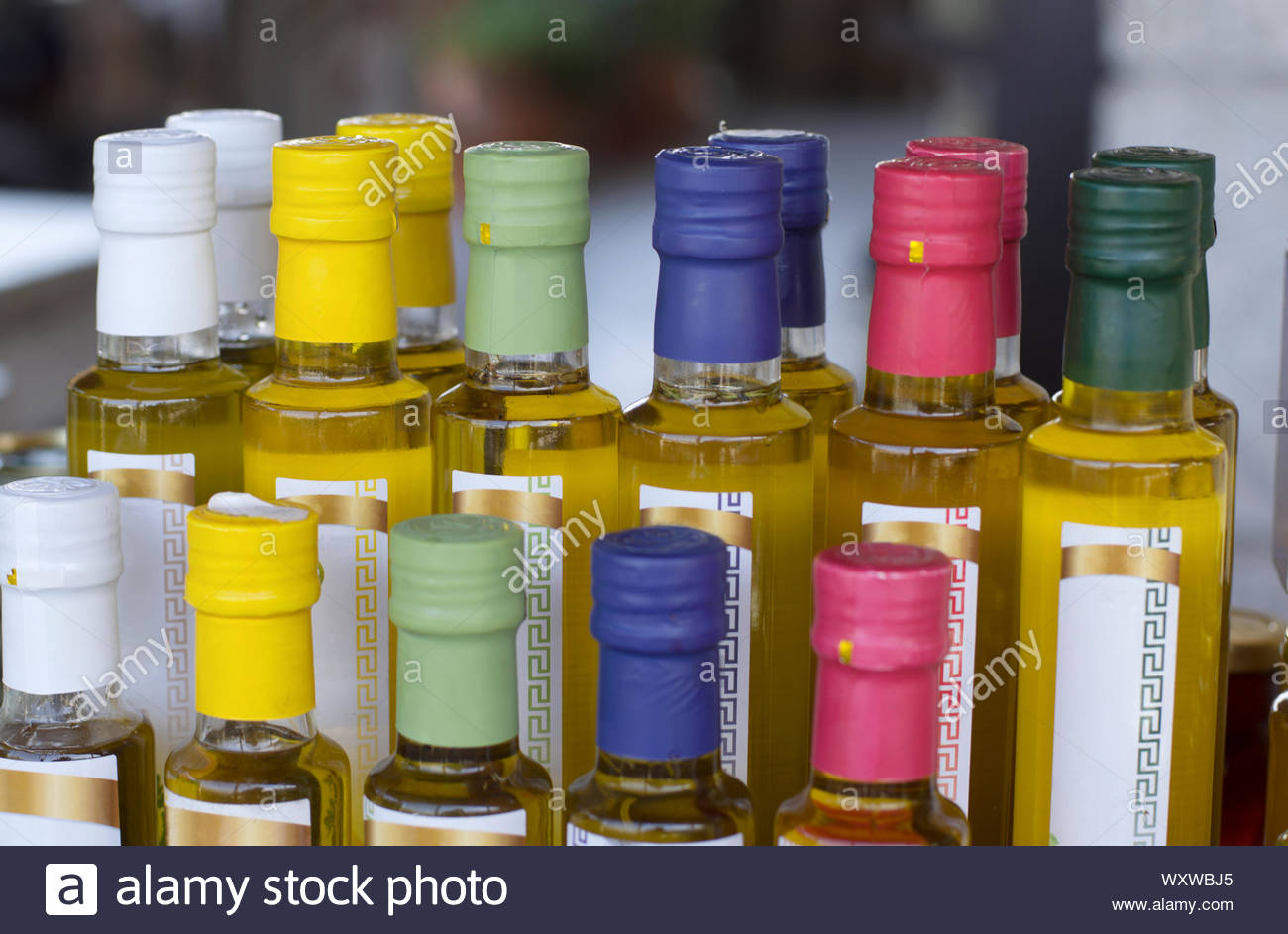Glass olive oil bottles without trademark with colorful sealed stoppers and greek ornament on blurred background closeup Stock Photo