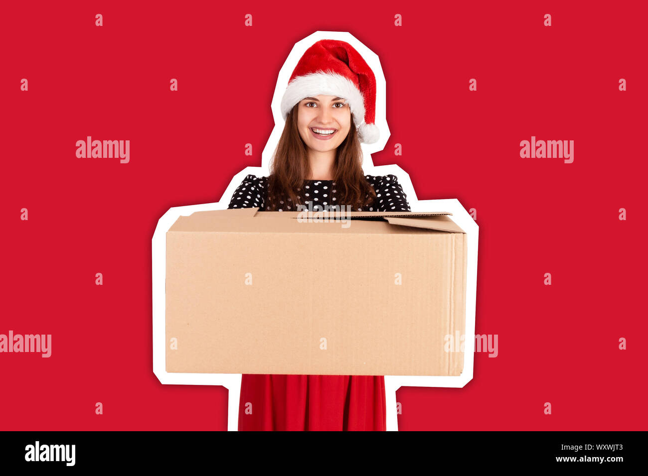 Cheerful happy girl in christmas hat giving a big carton present with blue ribbon. Magazine collage style with trendy color background. holidays conce Stock Photo