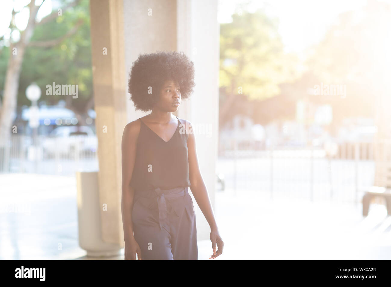 Young beautiful stylish curly woman on the street. Sunny day natural light. Summer fashion concept. Closeup. Stock Photo