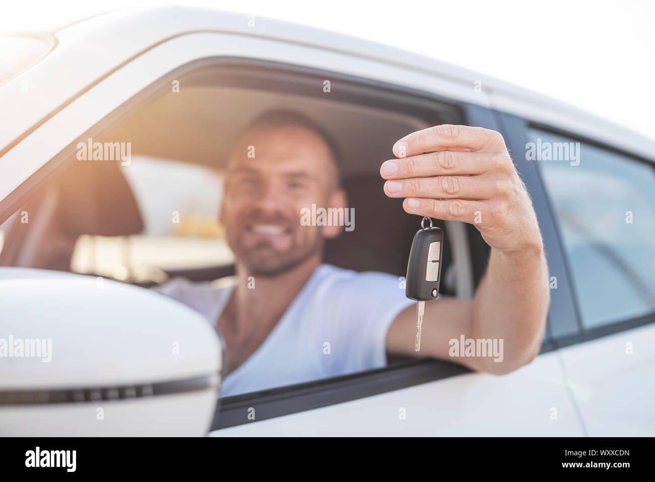 A man in a white car shows a key. Stock Photo