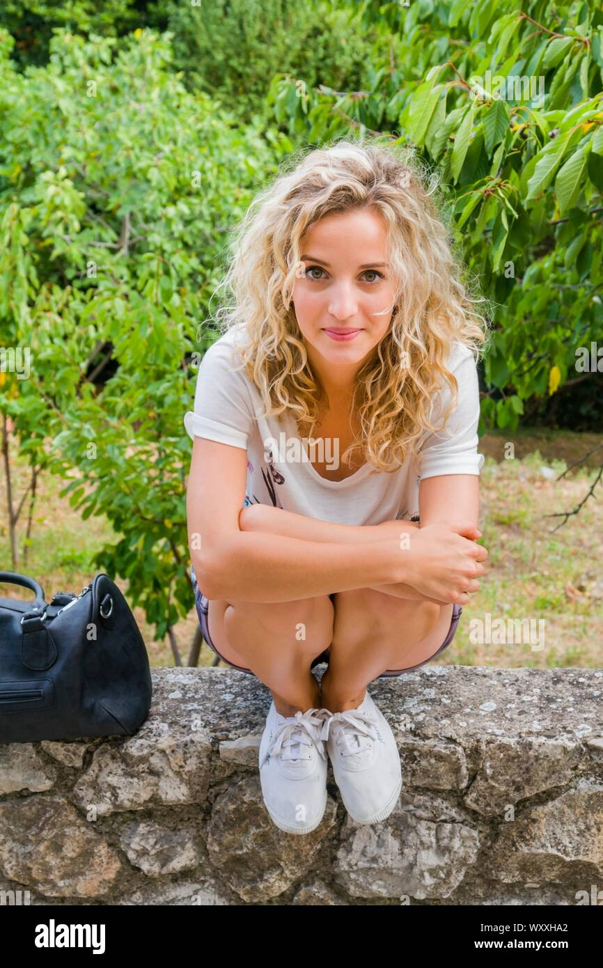 Cute blonde haired teen girl next door is squatting on stone wall waiting wait looking at camera eyeshot squatter Stock Photo