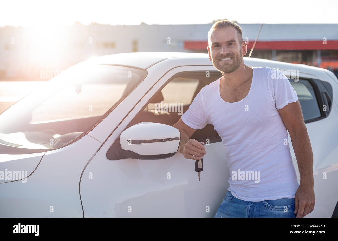 A male driver stands near a car with a key in his hand and smiles. Stock Photo