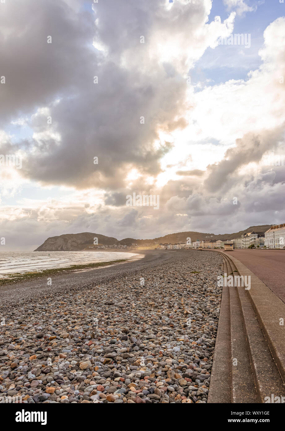 A view of Llandudno's curving shoreline with dramatic clouds.  The Little Orme headland is in the distance and sun rays illuminate a field. Stock Photo