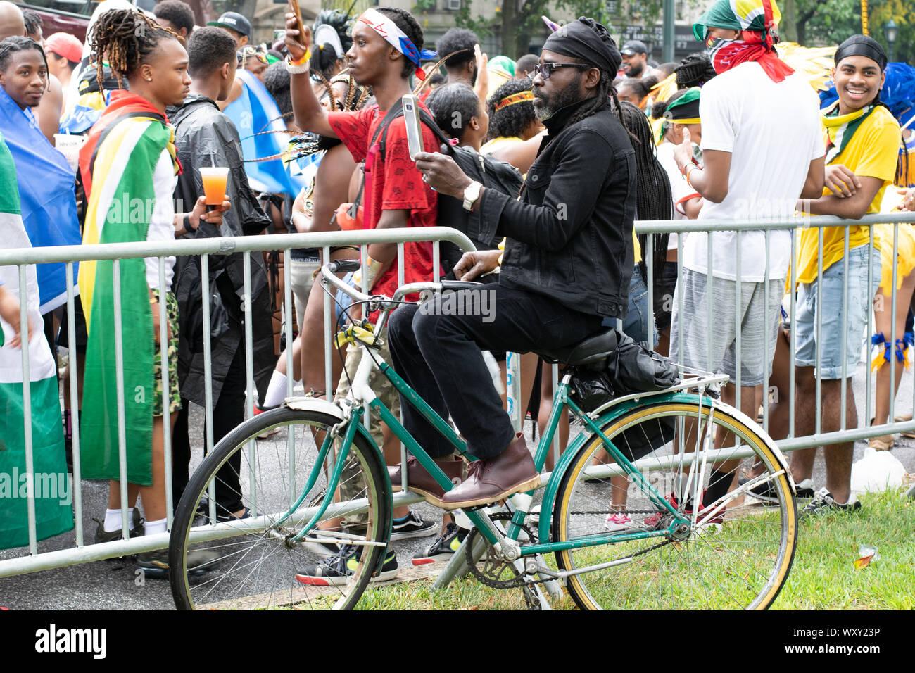 Hinter dem Zaun, an welcher die West Indian Day Parade entlang geht, sitzt ein Mann auf seinem Fahhrad und macht Fotos mit seinem Handy von den bunt a Stock Photo