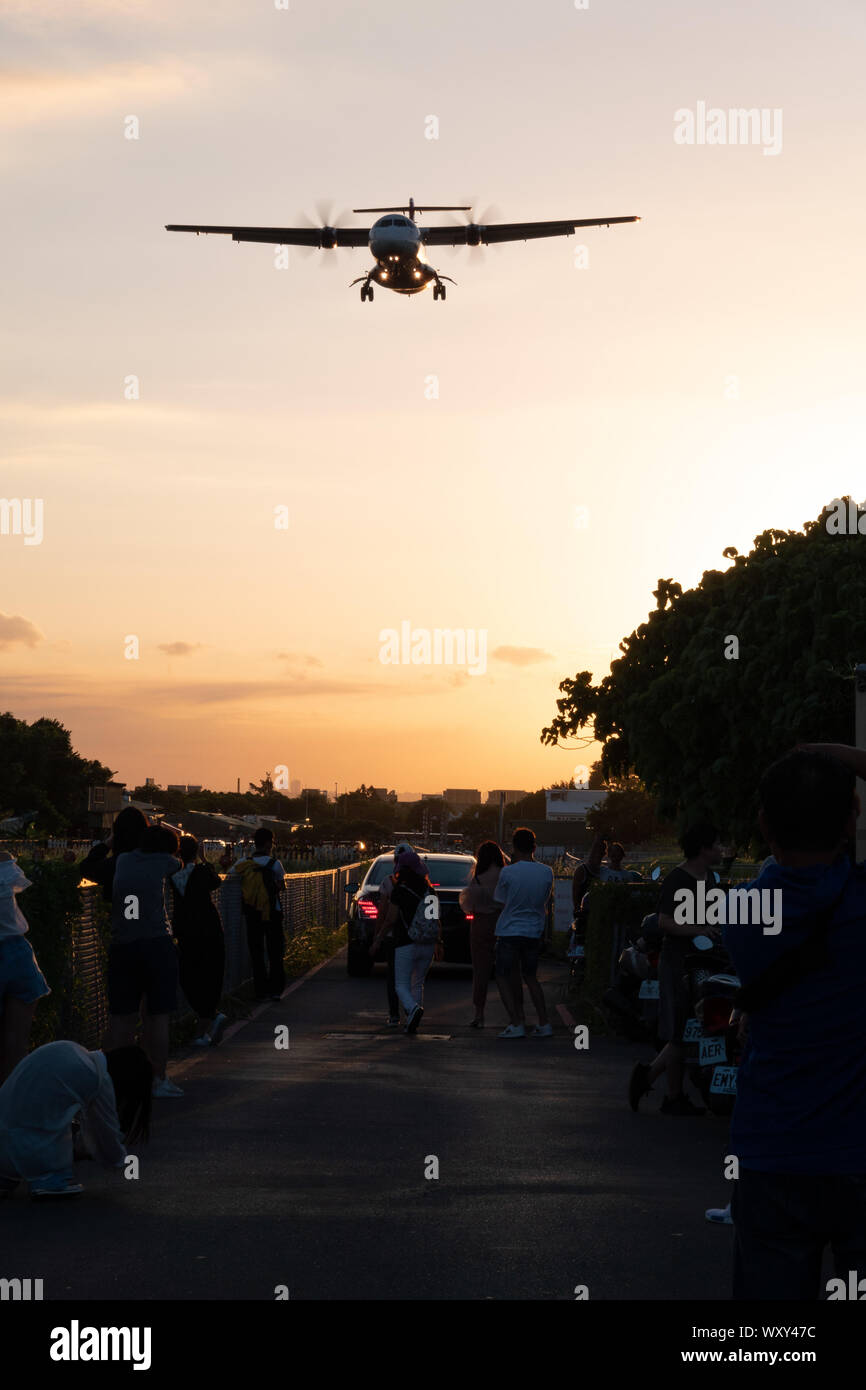 """Spectators watch and take photos from """"Airplane Alley"""" as a plane makes its approach to Songshan Airport, Taipei during sunset Stock Photo"""