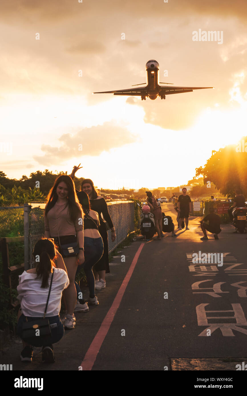 Spectators pose for photos while a McDonnell Douglas MD-82 screams over their heads on approach to Songshan Airport, Taipei Stock Photo