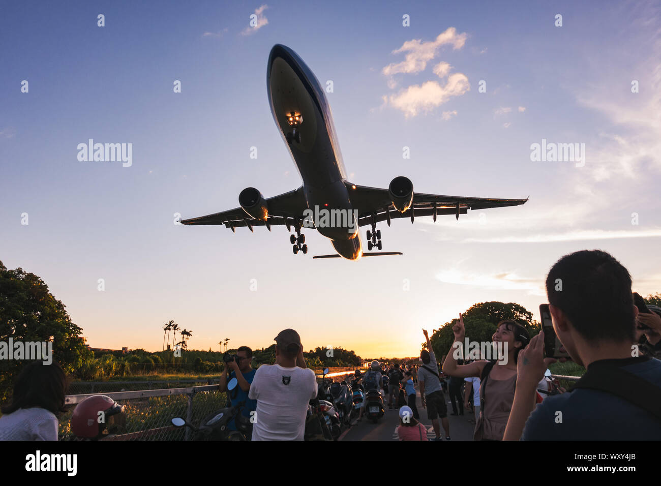 Spectators pose for photos as an Airbus A330-300 flies very low over their heads on approach to Songshan Airport, Taipei Stock Photo
