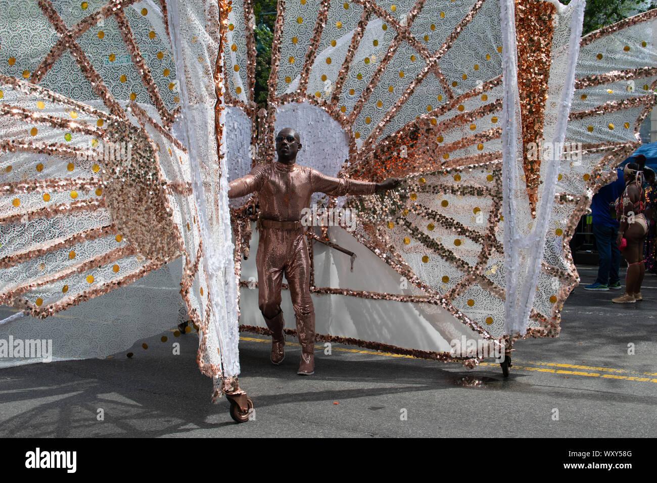 Ein Mann hat sich ein Kostüm erstellt, das wie ein Schmetterling anmutet. Auf Rollen präsentiert der Mann stolz sein Kunstwerk und geht im ZickZack an Stock Photo