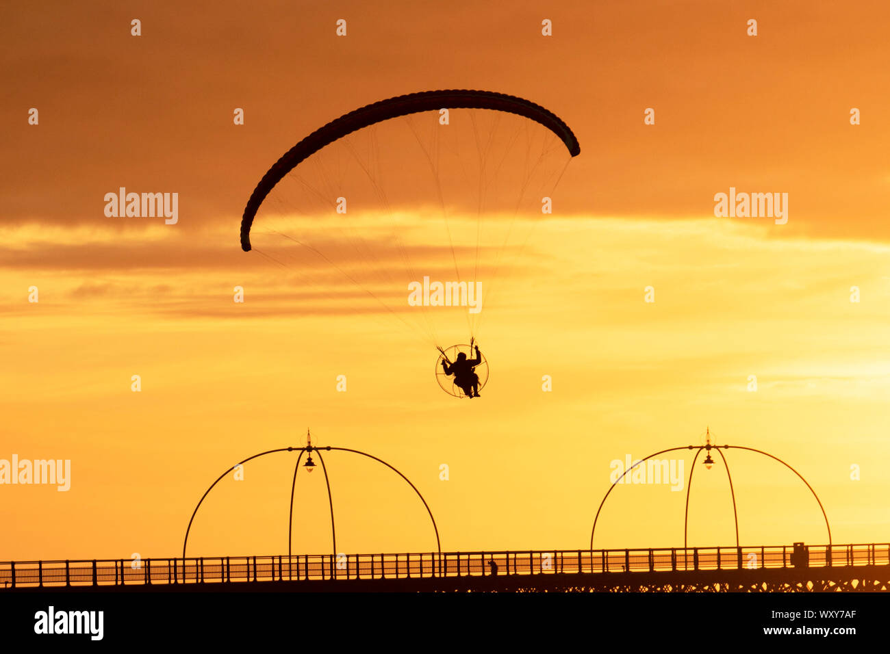 Southport. Merseyside. UK Weather. 18th Sept, 2019. UK Weather; Sunny colourful end to the day as powered hand glider silhouetted in the evening sun, takes a powered flight in light winds as the sun sets in Southport. Paramotor flying machines & Stunt flying as the sun sets; a hand glider silhouette against orange clouds, enjoying flying over the Irish Sea coast. Credit:MWI/AlamyLiveNews. Stock Photo