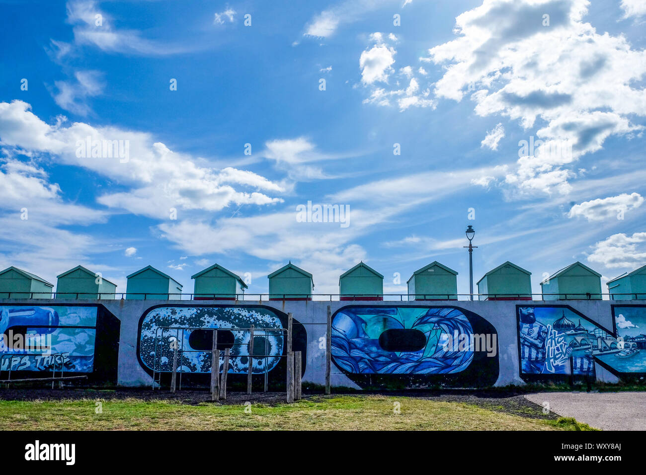A line of beach huts ontop of a congrete wall with graffiti in the top half of the photo is a big blue and white cloudy dramatic sky, Hove, Brighton, Stock Photo