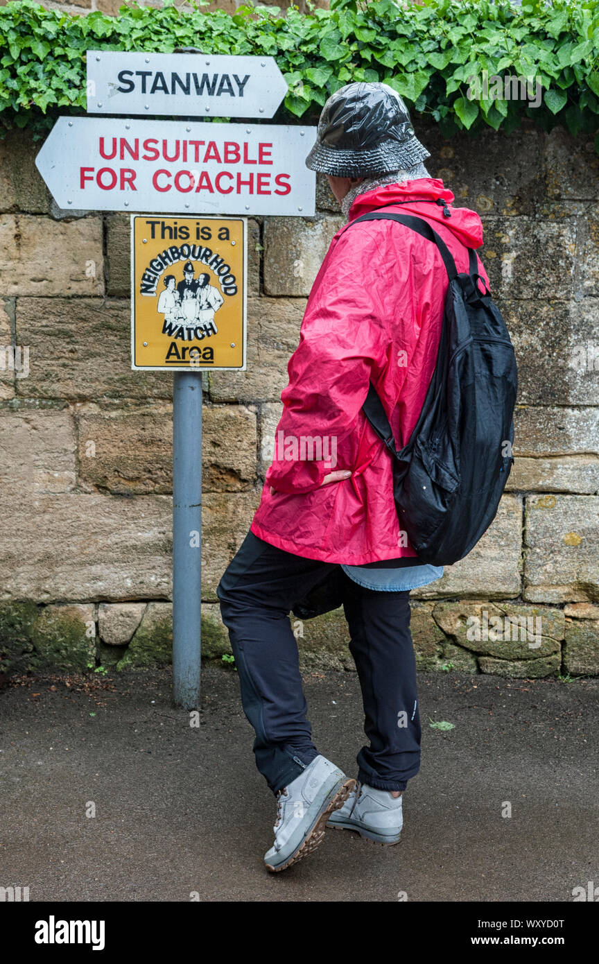Unindentified woman looking at signs with directions in the Cotswold village of Stanway, Gloucestershire, Cotswolds, UK Stock Photo