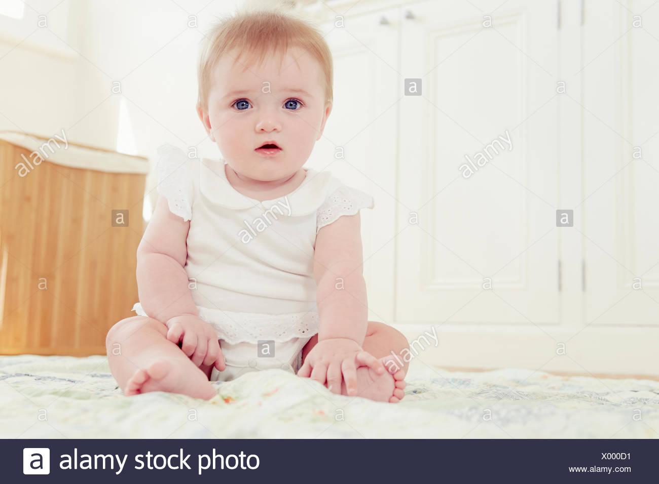 Portrait baby girl sitting on floor - Stock Image