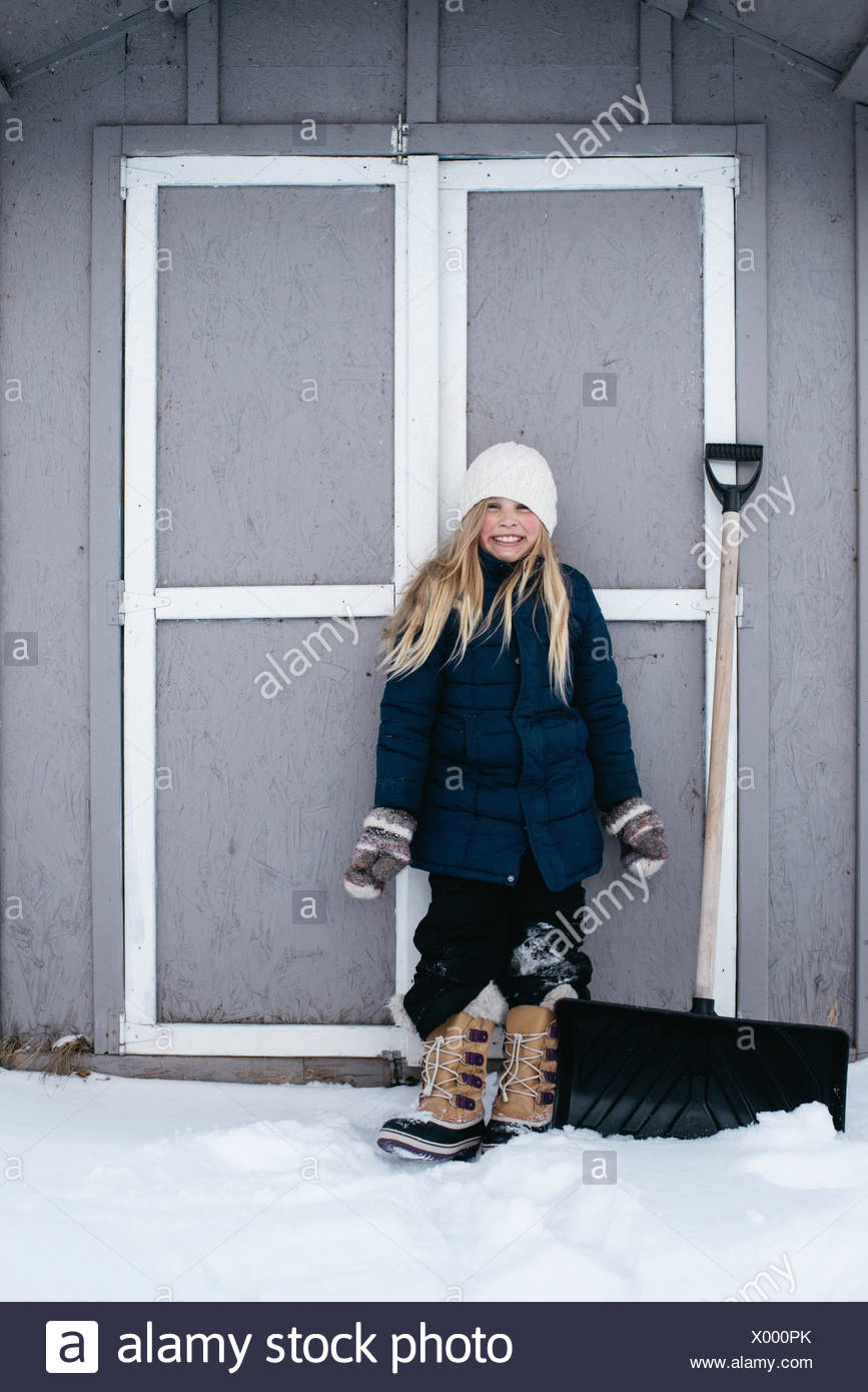 Girl grinning with excitement at snow - Stock Image