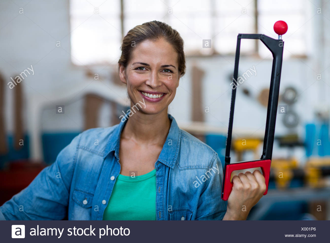 Happy female carpenter holding coping saw - Stock Image
