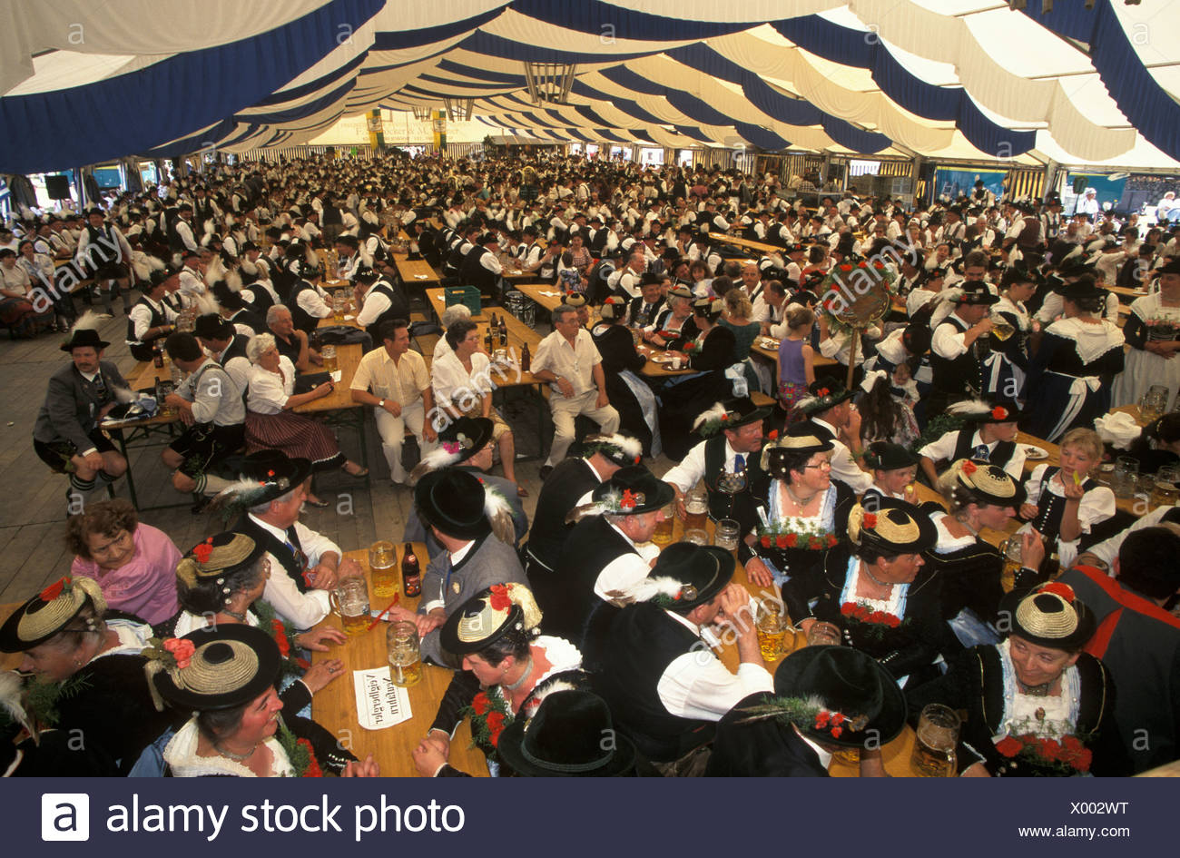 Attendees dressed in traditional costume sitting in the festival tent during the Loisachgau Festival in Egling, Upper Bavaria,  Stock Photo