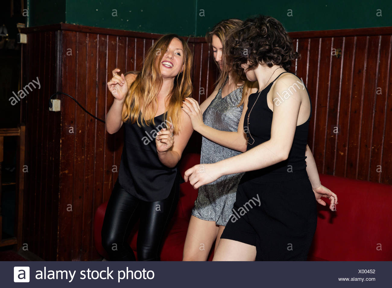 Three adult female friends dancing together in club on night out - Stock Image