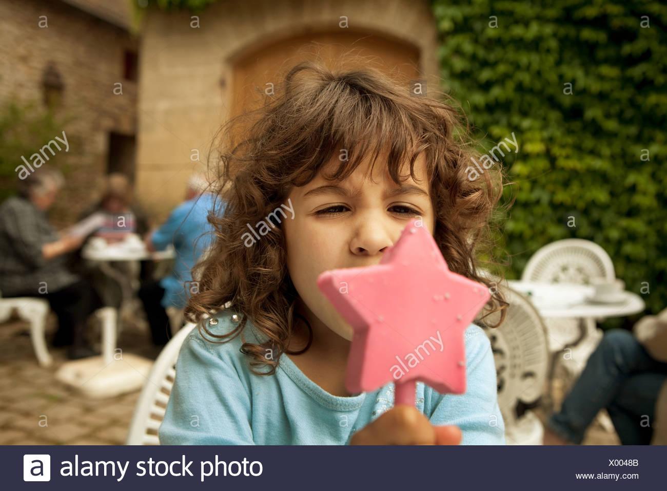 Girl eating star shaped ice cream - Stock Image