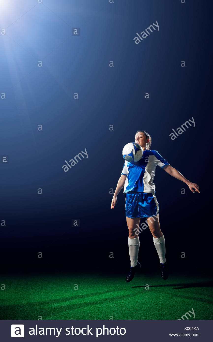 Young female soccer player controlling ball - Stock Image