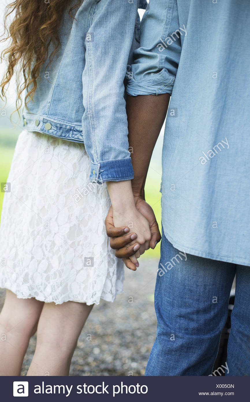 A young man and woman a couple holding hands. Back view. - Stock Image