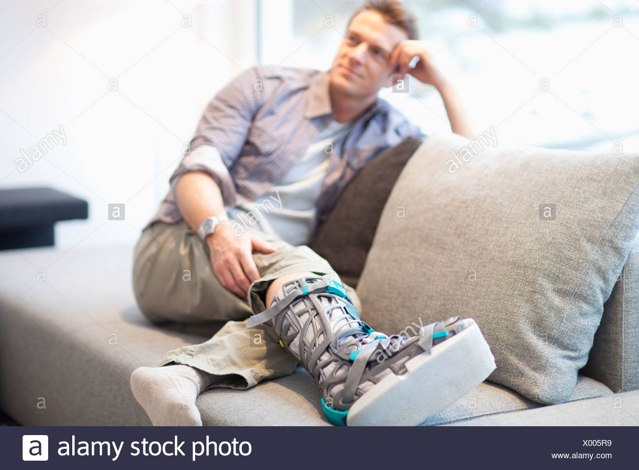 Mid adult man in foot brace relaxing on sofa - Stock Image