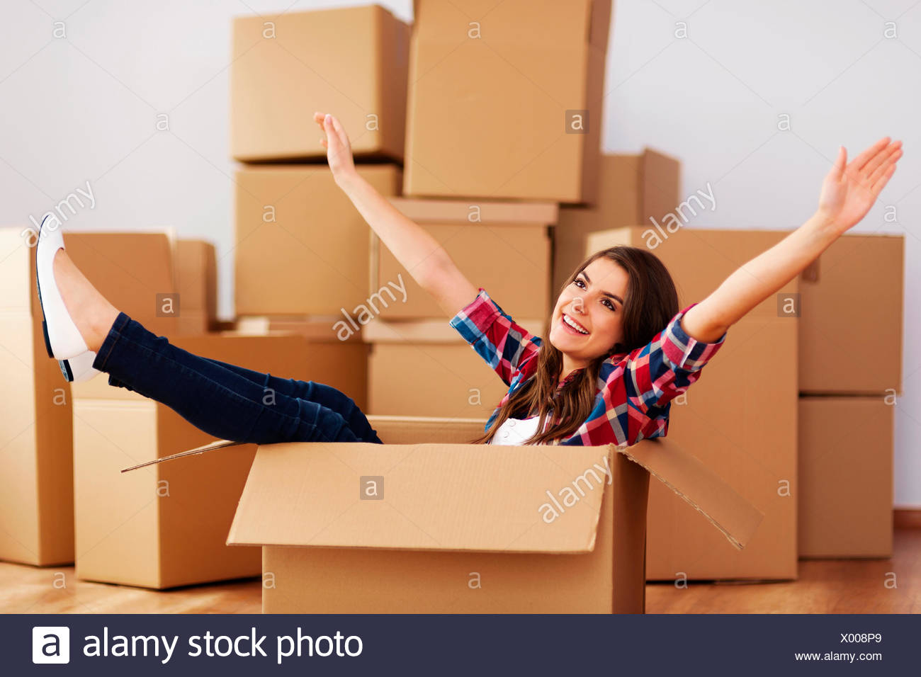 Cheerful woman sitting in a cardboard box Debica, Poland - Stock Image