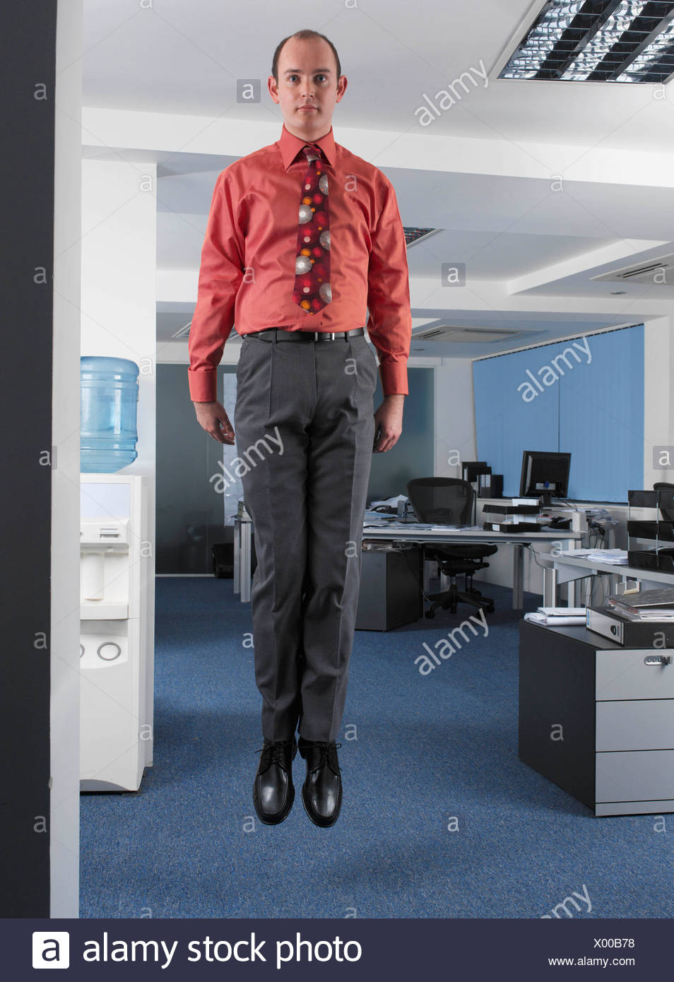 Office worker suspended in mid air - Stock Image