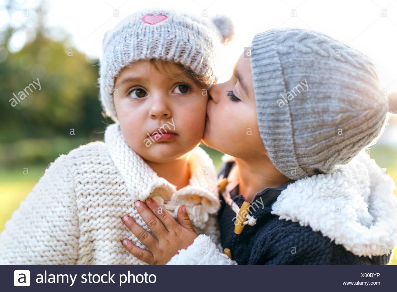 Little girl kissing another little girl - Stock Image